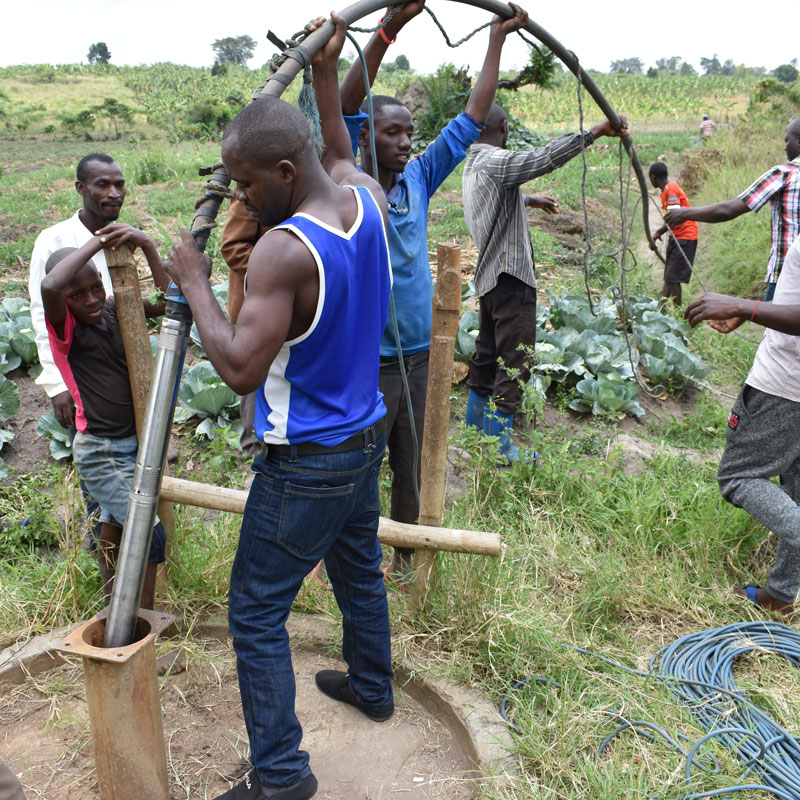 A group of men feeding a long pipe into the ground, which will tap into an underground water source