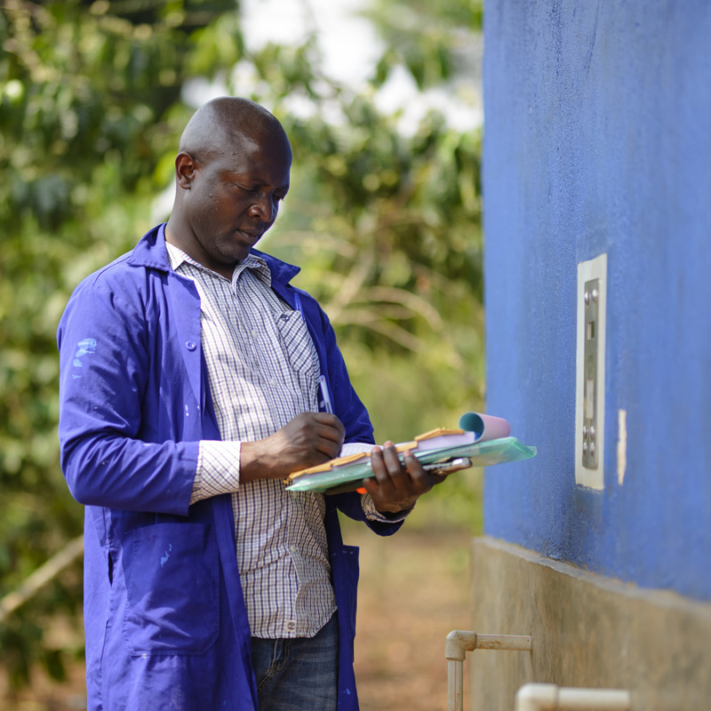 A Water Compass technician checking the electronic payment system on a solar-powered water point