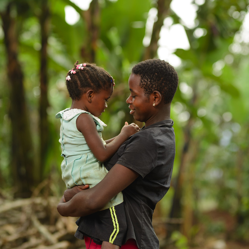A woman standing outside amid trees, holding her young daughter and smiling