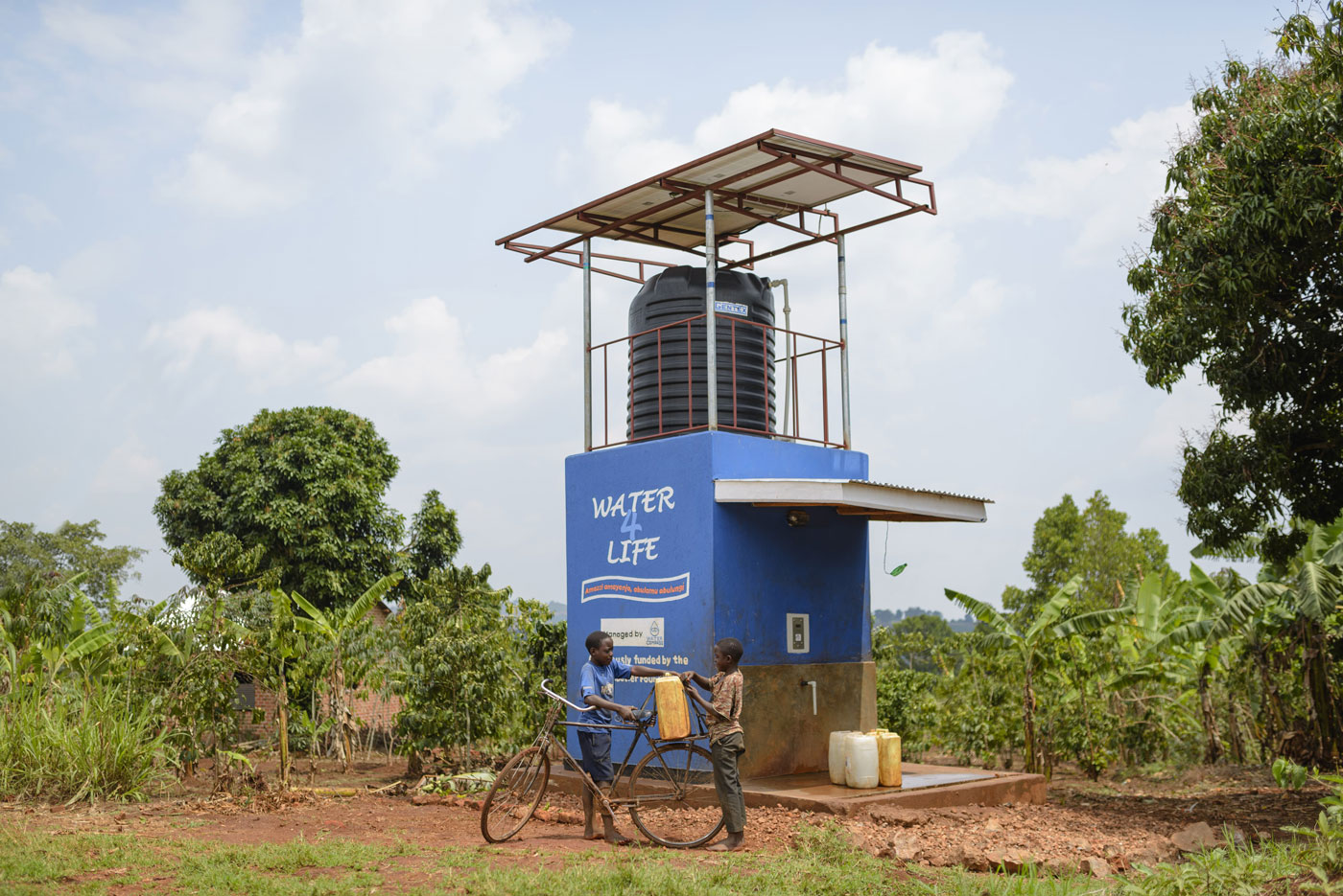 A Water Compass solar-powered water point among trees, two boys loading full jerry cans onto a bicycle