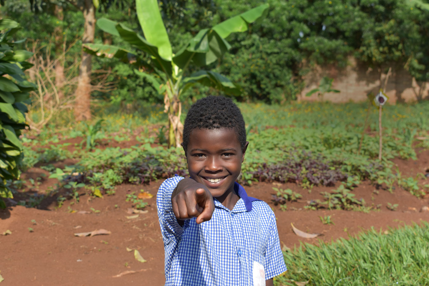A young boy pointing directly at the camera with a big smile
