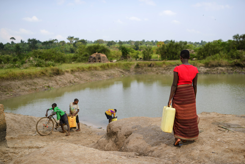 A woman and her children collecting water in jerry cans from an open water source, which is brown and dirty