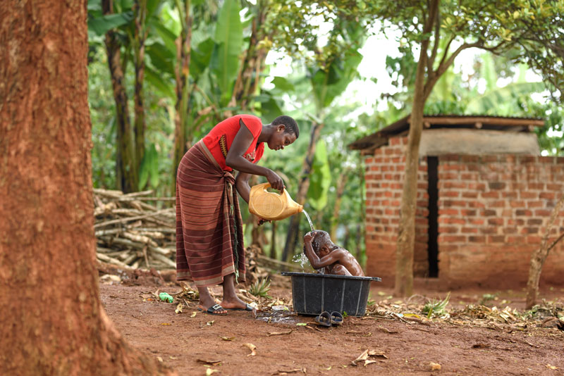 A mother bathing her child in a large plastic tub outside of her home