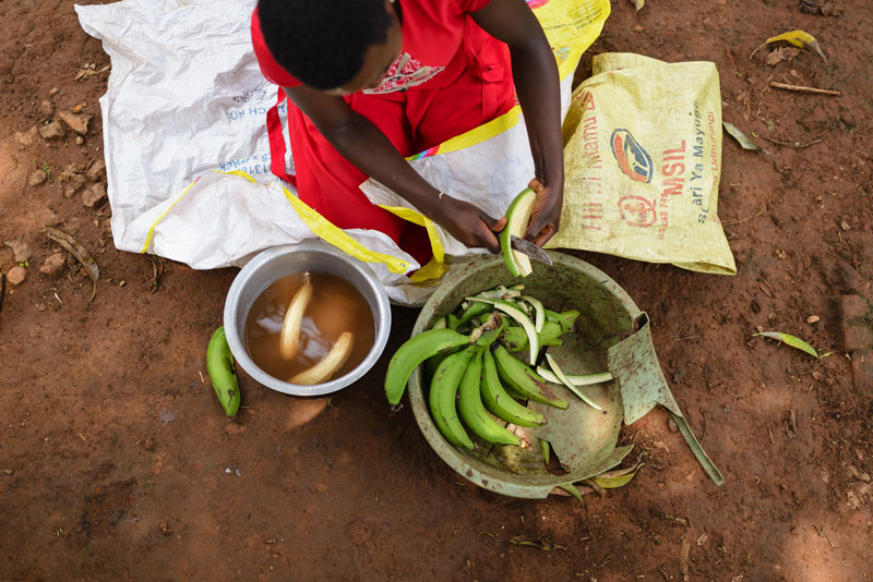 A woman cutting up bananas and placing them in a bowl of brown, dirty water