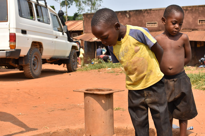 Two very small little boys peeking into an unfinished pipe that will eventually become a water point
