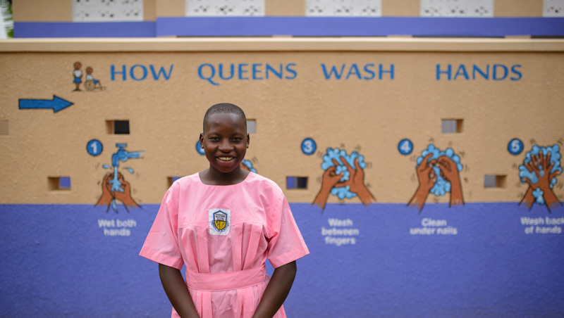 A young woman in a pink school uniform standing in front of the new bathrooms installed by Water Compass at her school