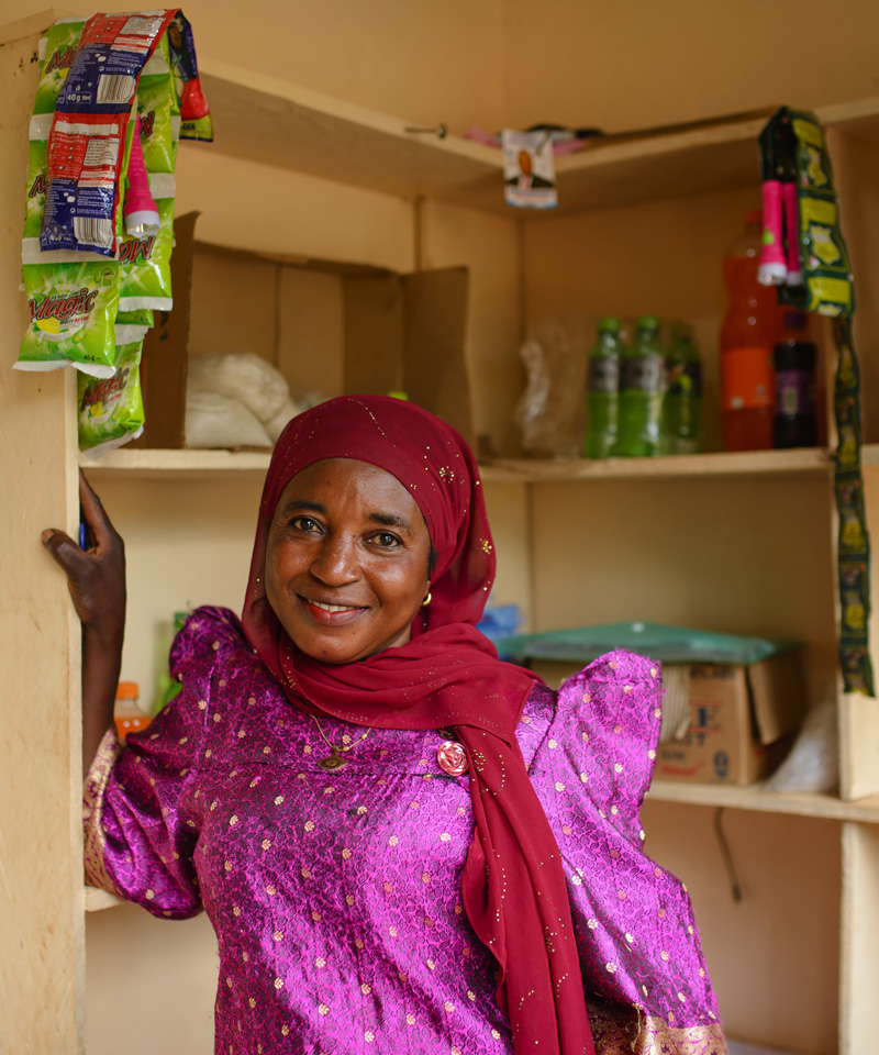 One of Water Compass's female local agents standing in the small store she runs on the site of a water point