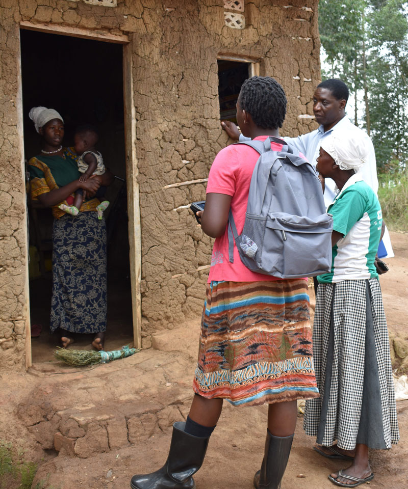 Three Water Compass staff members talking to a woman at her home about her community's needs