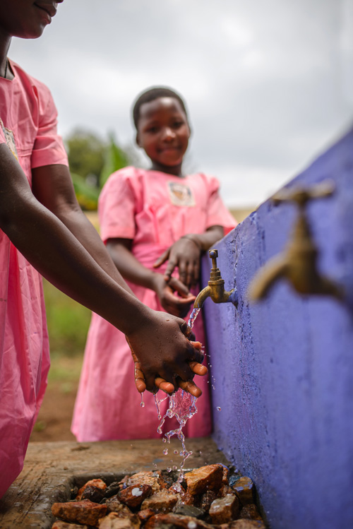 Female students washing their hands at a new hand-washing station at their school