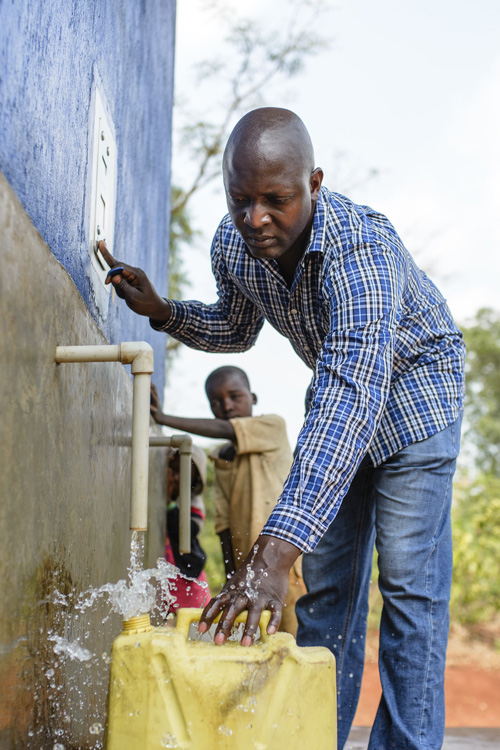 A man filling up a yellow jerry can with clean water