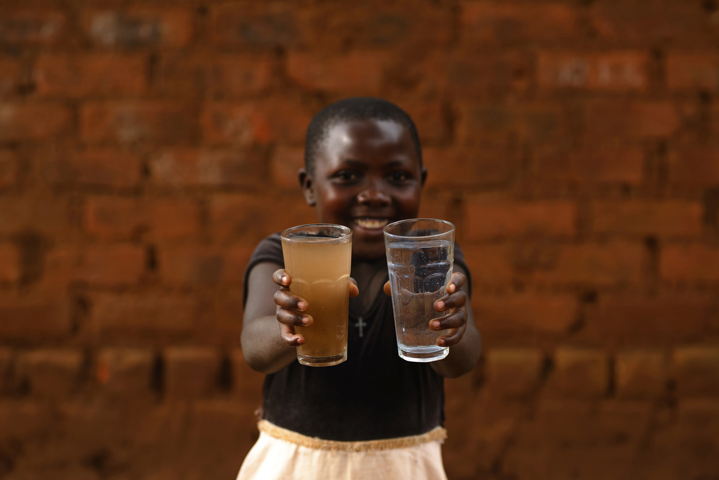 Little girl holding two glasses of water - one dirty and one clean