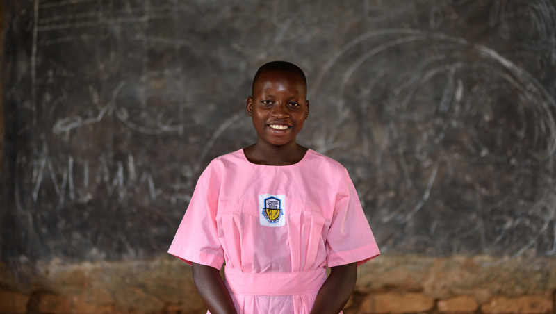A young woman in a pink school uniform standing in front of a chalk board in her classroom, smiling