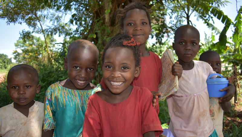 A group of five adorable young children smiling