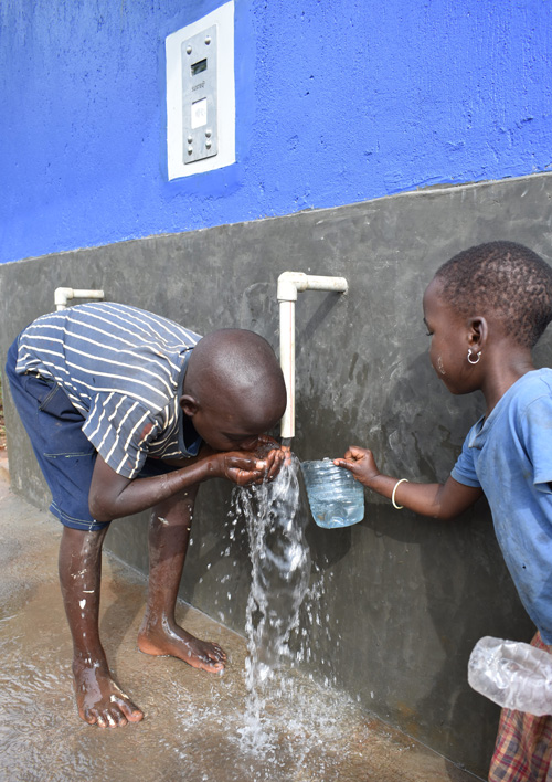 Two young children drinking clean water out of a Water Compass water point