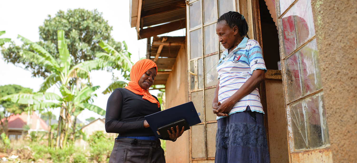 A female Water Compass staff member surveying a woman in the community about her community's water needs