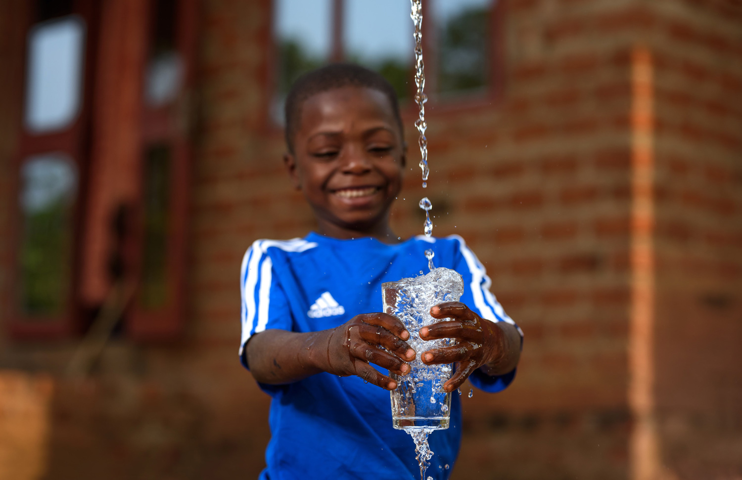 A stream of water being poured into a glass of water held by a happy little boy.
