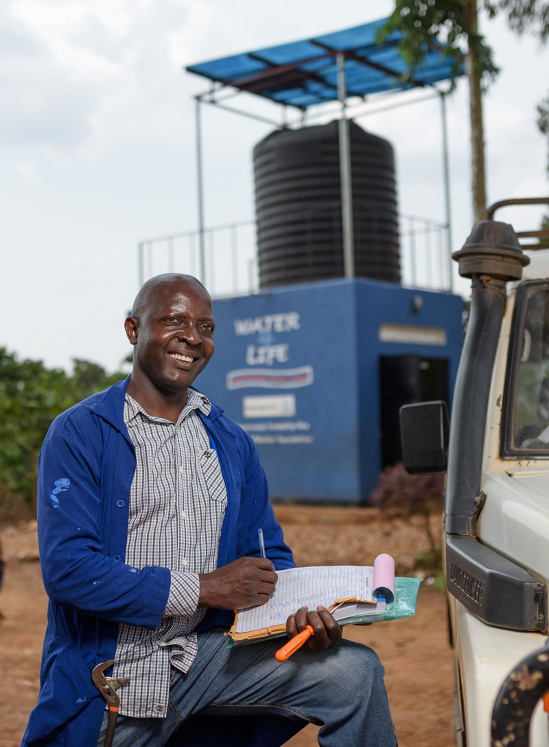 A Water Compass staff member with a clipboard in front of a water point, providing basic maintenance