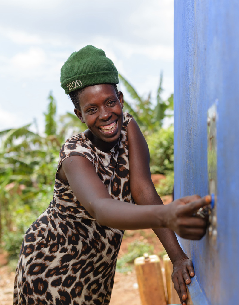 A woman using the electronic payment system on a Water Compass solar-powered water point