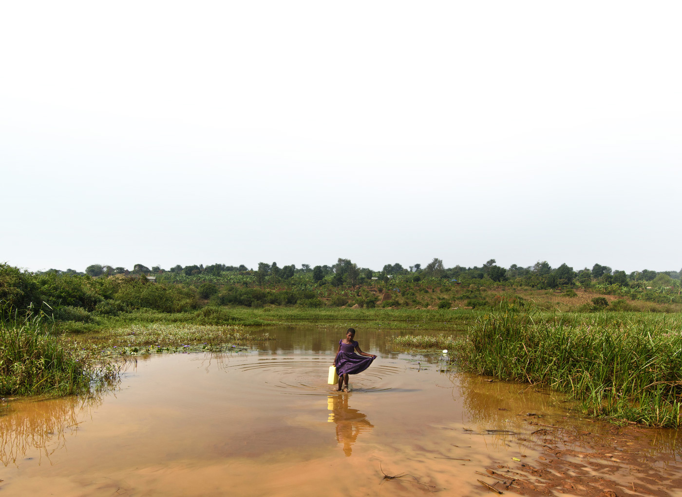 A little girl in a purple dress collecting water from a dirty water source