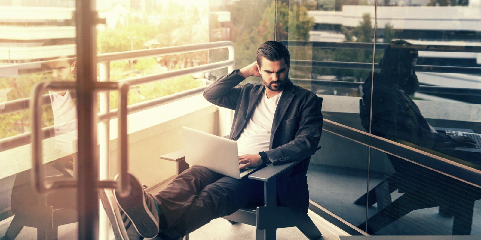 Man sitting outside and looking concerned about something on his laptop