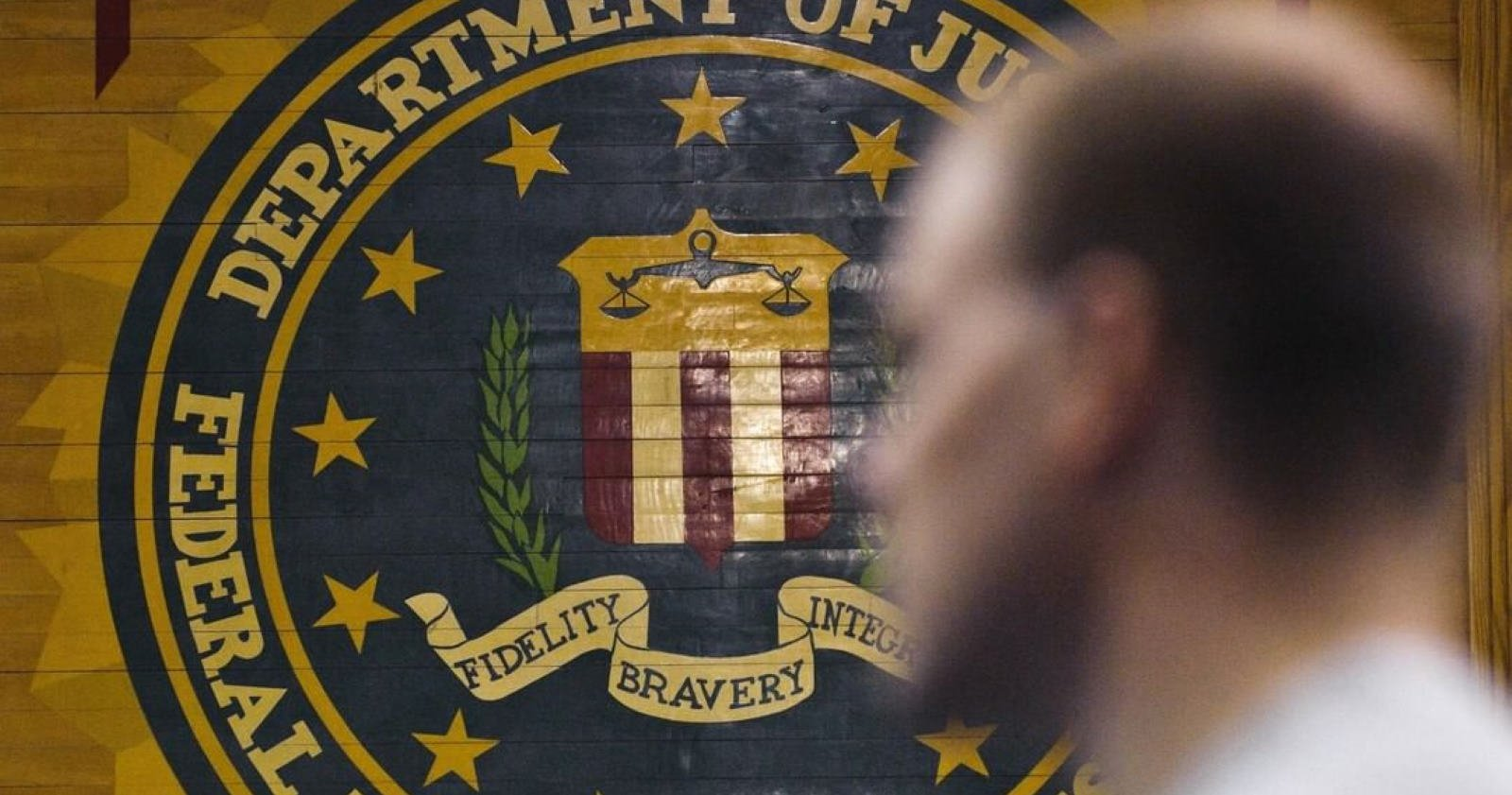 Picture of a man walking past a FBI banner.