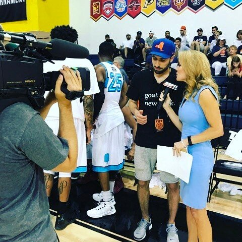 Photo of Griffin Taylor talking to ESPN reporter at a basketball game