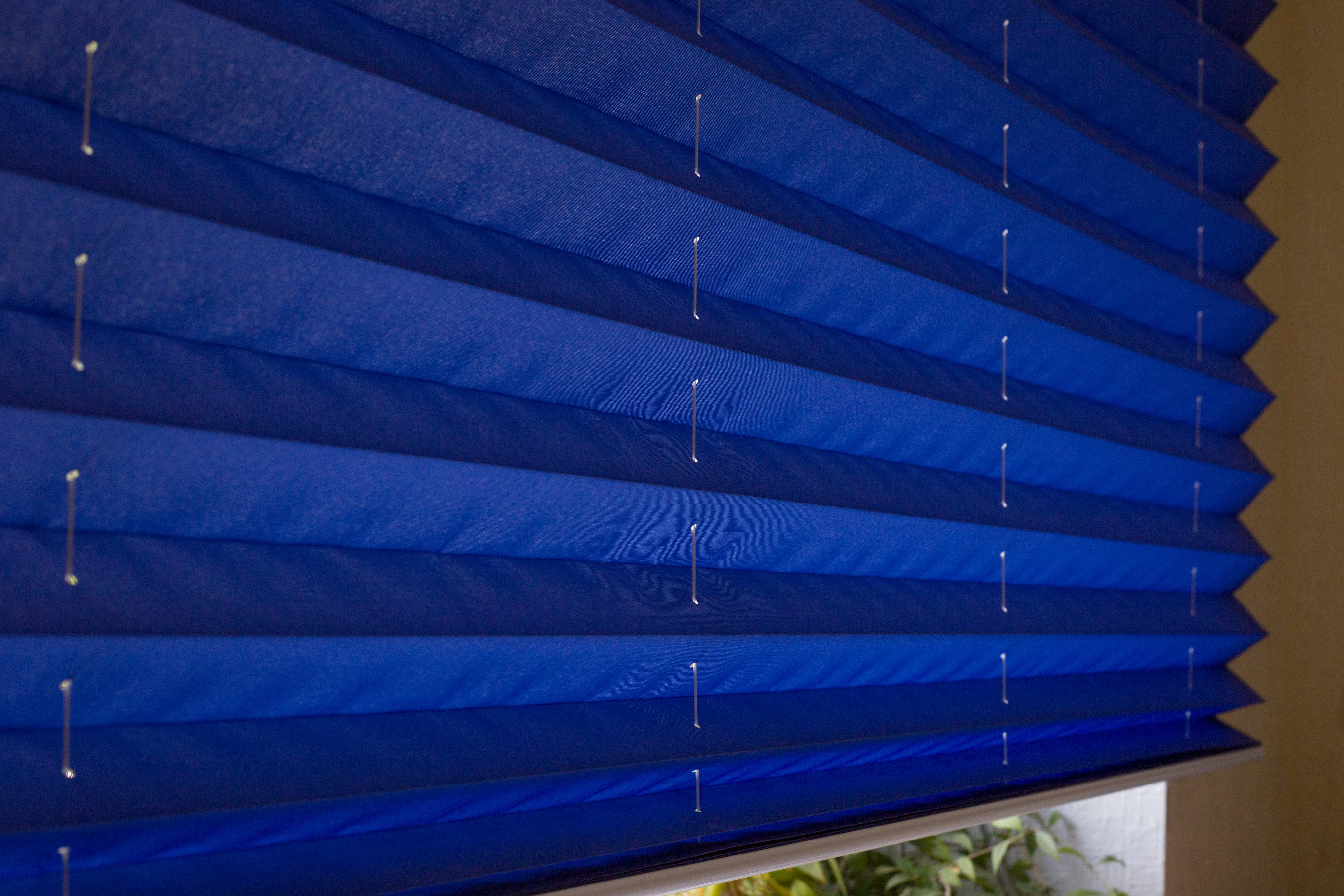 A free hanging blue pleated blinds