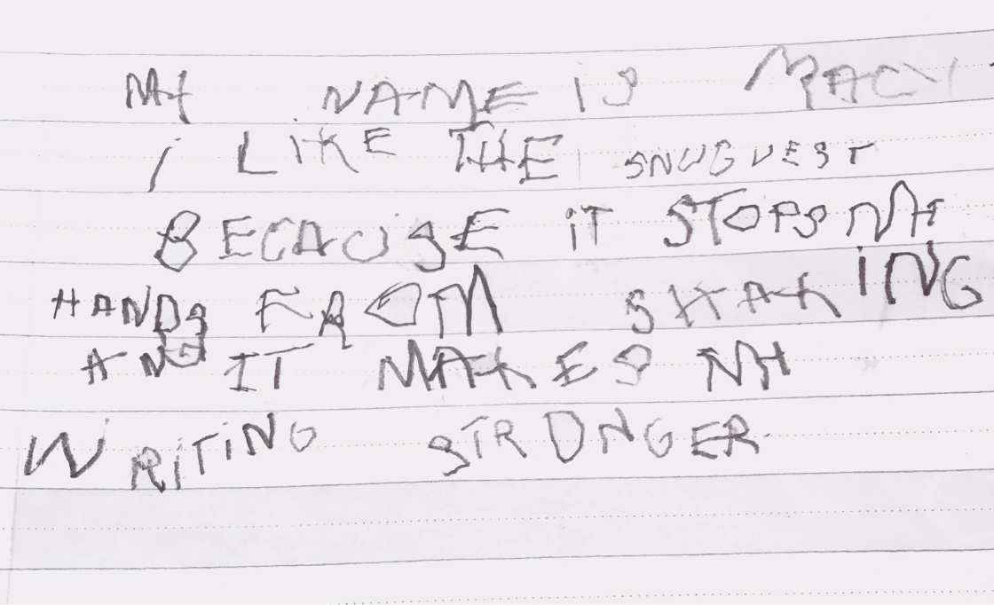 Shaky handwriting that reads: My name is Macy. I like the Snug Vest because it stops my hand from shaking and it makes my writing stronger.