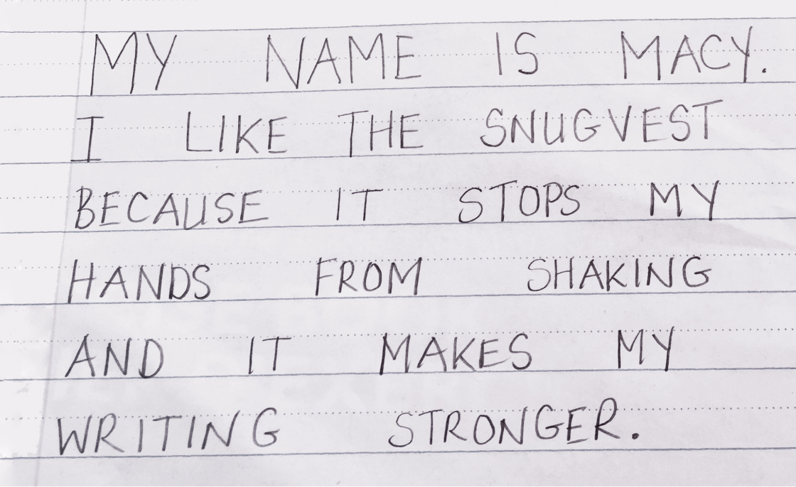 Neat handwriting that reads: My name is Macy. I like the Snug Vest because it stops my hand from shaking and it makes my writing stronger.