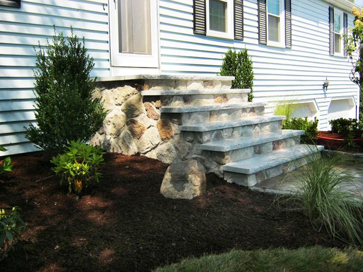 new england landscaper Shrewsbury, MA natural veneer stone retaining wall, stairs with granite treads, plantings
