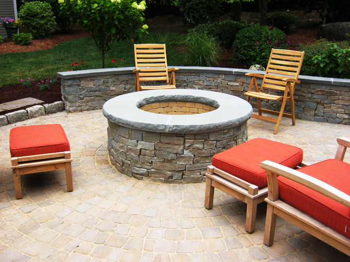 new england landscaper Reading, MA natural stone fire pit, rock face retaining wall with a bluestone cap, paver patio, irrigation