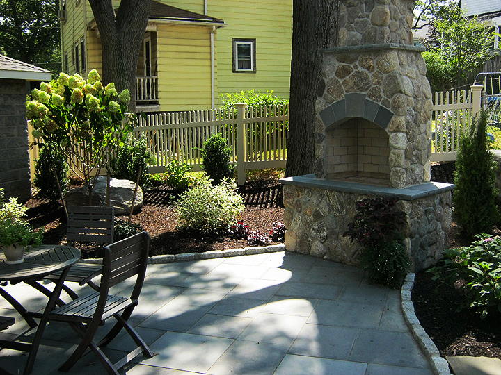 new england landscaper Melrose, MA boston blend round stone outdoor oven / fireplace with bluestone accents, plantings,  irrigation