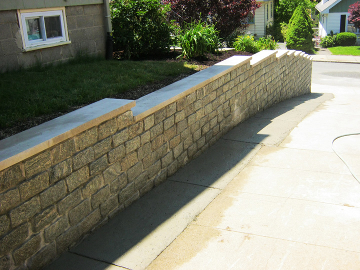 new england landscaper Medford Heights, MA cobblestone retaining wall with limestone cap