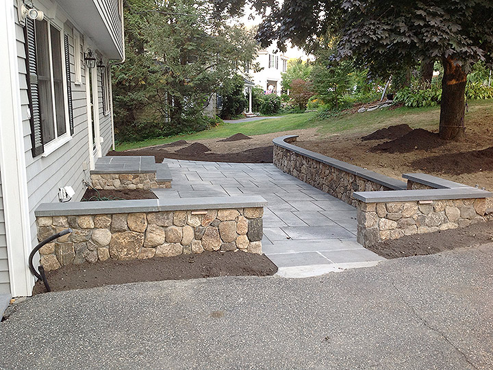 new england landscaper Melrose, MA natural rock retaining wall with bluestone cap, recessed lighting, stairs, patio, plantings, irrigation