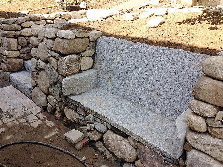 new england landscaper Medford, MA natural stone retaining wall, custom reclaimed historic granite bench, paver patio