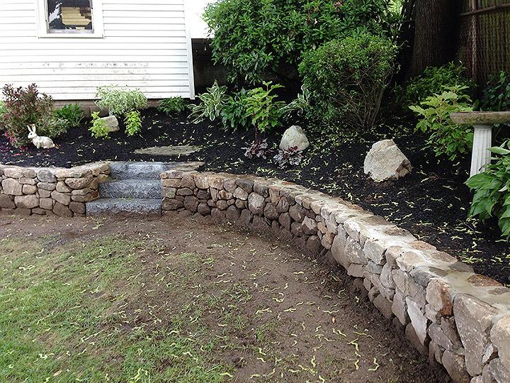 new england landscaper Medford, MA natural stone retaining wall, granite steps, plantings
