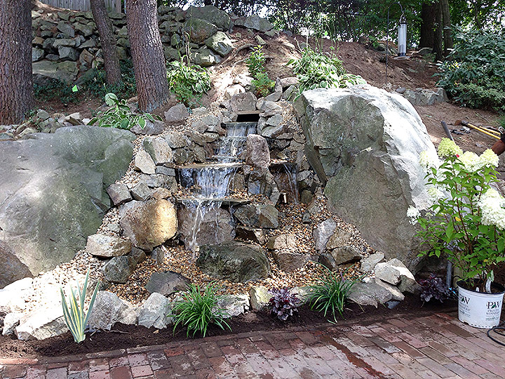 new england landscaper Stoneham, MA natural customized natural stone waterfall, plantings, lighting