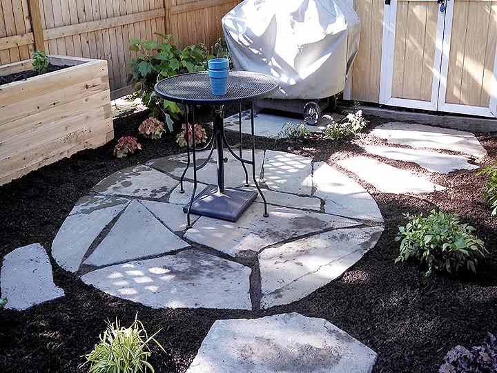 new england landscaper Cambridge, MA irregular bluestone patio, stepping stone path, raised cedar planting box, plantings