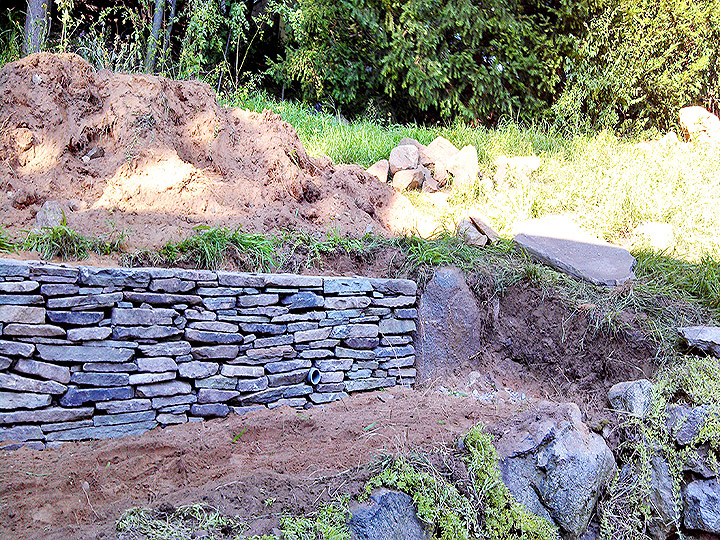 new england landscaper Arlington, MA natural stone retaining wall, drainage, decorative stone endpiece