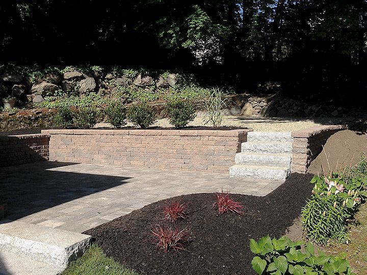 new england landscaper Arlington, MA concrete block retaining wall, paver patio, granite stairs, plantings