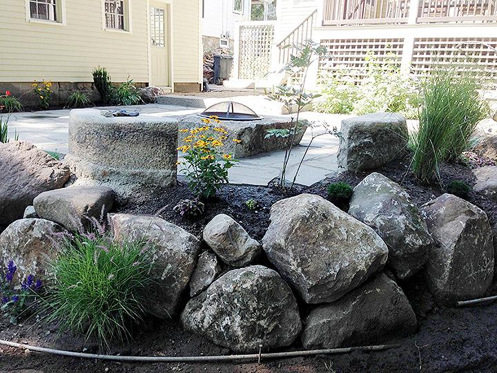 new england landscaper Melrose, MA irregular bluestone patio, reclaimed granite firepit, reclaimed granite benches, decorative rocks