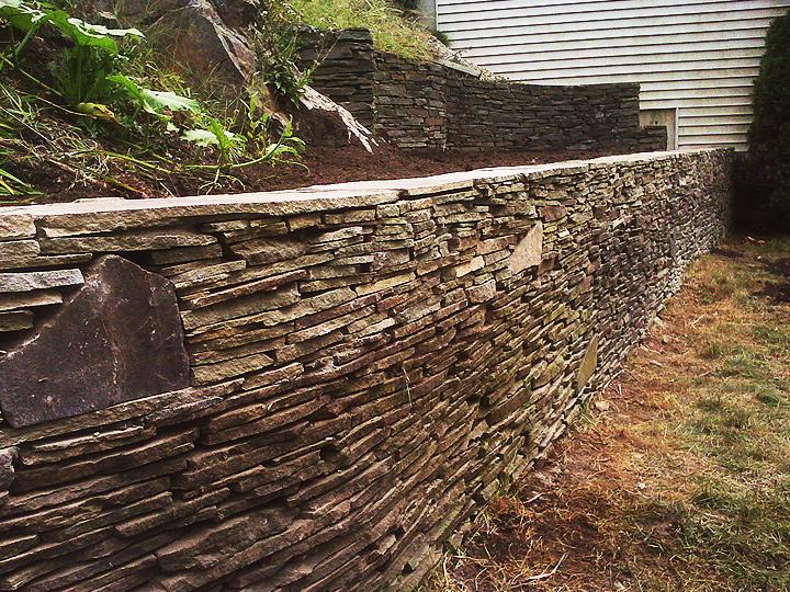 new england landscaper Lynn, MA irregular bluestone retaining wall with large stone accents