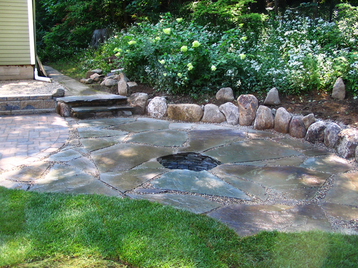 new england landscaper Winchester, MA paver patio and irregular blue stone patio with recessed fire pit