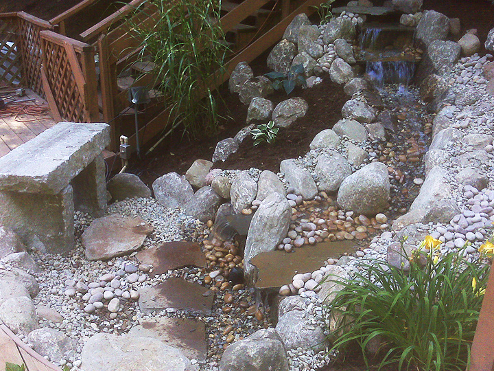 new england landscaper Glastonbury, CT curved deck, pool patio, granite bench, pondless watefall, plantings, landscape lighting