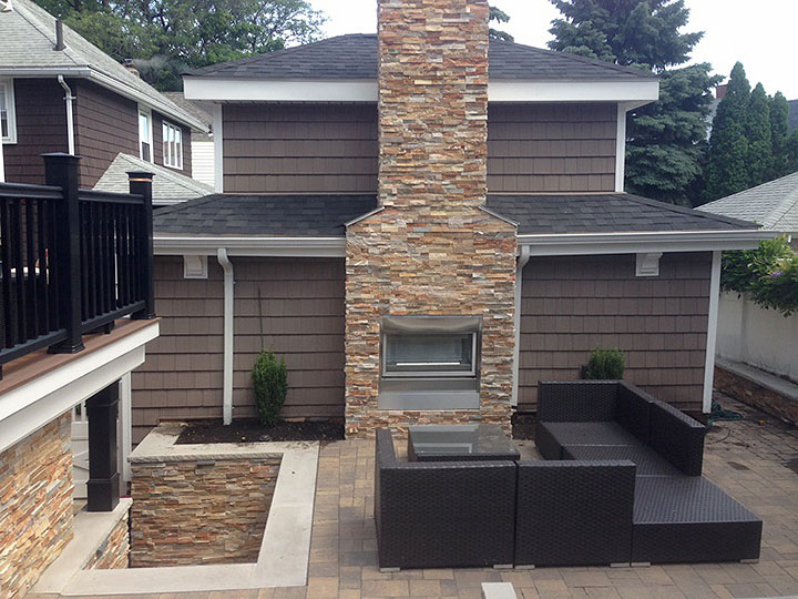 new england landscaper North Reading, MA paver patio, natural thin veneer stone wall and chimney, natural cap, outdoor foreplace, built-in lighting
