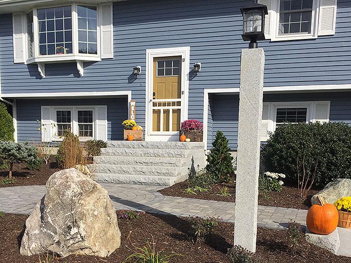 new england landscaper North Reading, MA reclaimed granite stairs, paver sidewalk, reclaimed grainite light post, landscape lighting, decorative large natural rocks, plantings