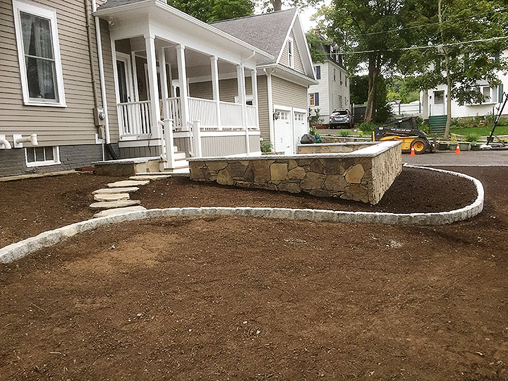 new england landscaper North Reading, MA curved cobblestone edge, natural stone patio, natural thin veneer stone wall, natural cap, natural stone path, irrigation, excavation, drywell