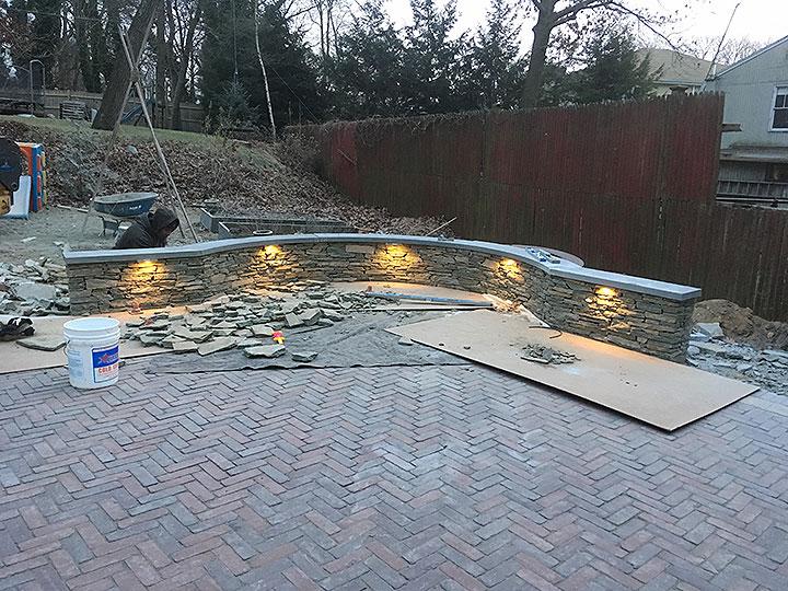 new england landscaper North Reading, MA natural stone wall, brick patio, cobblestone edge, built-in landscape lighting