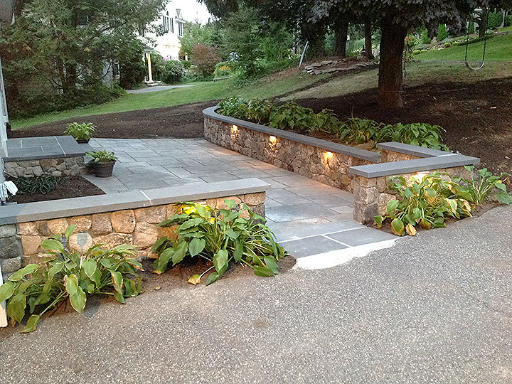 new england landscaper North Reading, MA natural stone wall, thermal bluestone patio, built-in landscape lighting, plantings