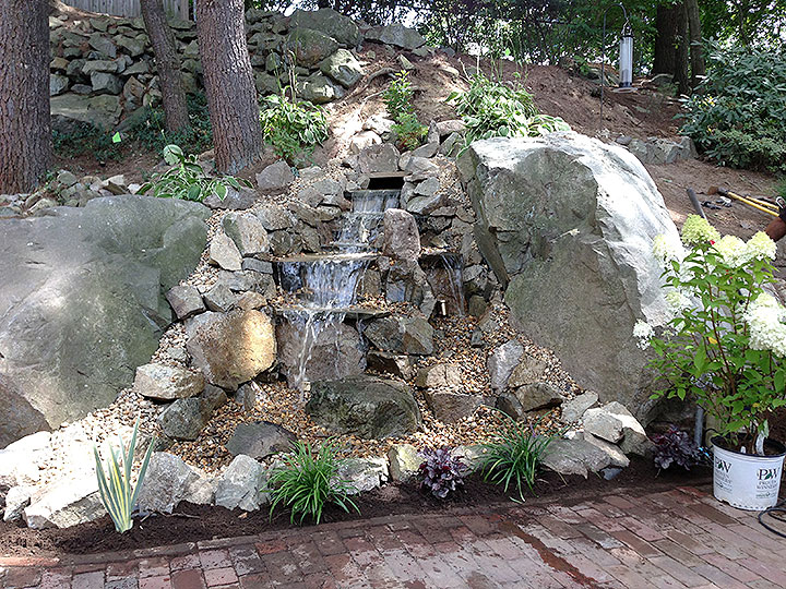 new england landscaper Andover, MA waterfall feature, ornamental large stones, plantings